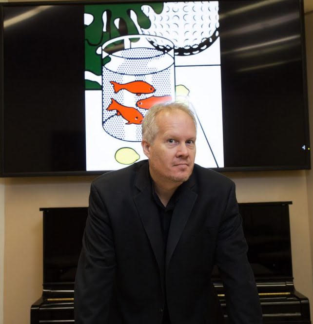 Kirk O'Riordan stands in front of a piano with a piece of art projected behind him.