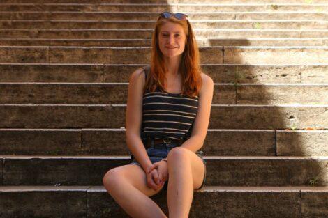 Allison Paglia sits on stone steps