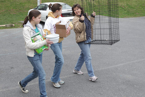 Becky Rosenbauer and her two daughters carry items while volunteering for an animal shelter.