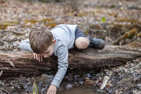 Grant lays on a log at a creek