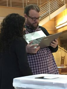 John Boyer holds a laptop while talking with student debate competitor Vanessa Milan '16