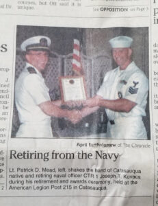 Joseph Kovacs shakes the hand of a naval officer while accepting a placque for his retirement from the Navy. Both are in uniform.