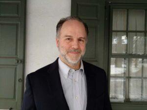 Professor Eric Ziolkowski stands in front of a door.