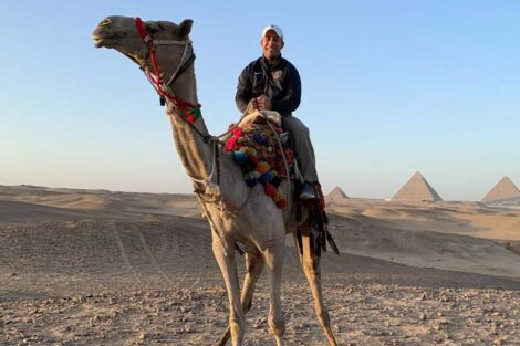 Josh Azer rides a camel in the desert with pyramids in the distance behind him.
