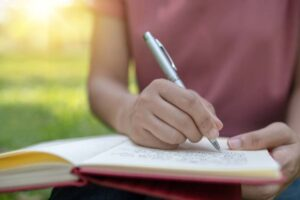A person writes outside in a notebook