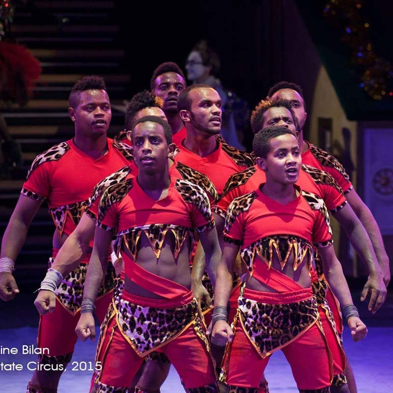 Matwos Tadesse and his fellow circus acrobats wear red and leopard print during a performance in Belarus.
