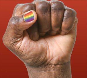 A fist with its thumbnail having rainbow nail polish