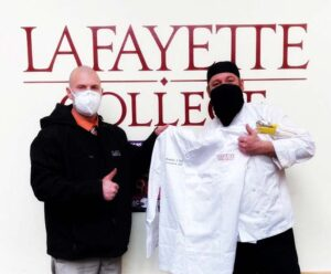 Beandan Duff and a Dining Services colleague together hold up his new white executive chef uniform