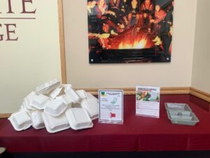 A pile of white Eco-clamshell food containers on a table next to a couple of informational signs and another food container, all on a red tablecloth