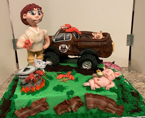 A cake by Kathy Kaneps with a person wearing glasses, lobsters, a sleeping pig, bacon, and a van on top of it