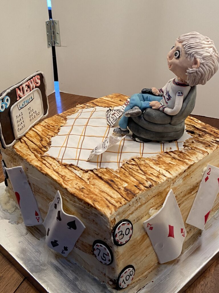 A cake by Kathy Kaneps with frosting decorations on top of a person wearing a New York Giants shirt and sitting on a chair watching the lottery numbers on channel 69 news and frosting playing cards on the sides