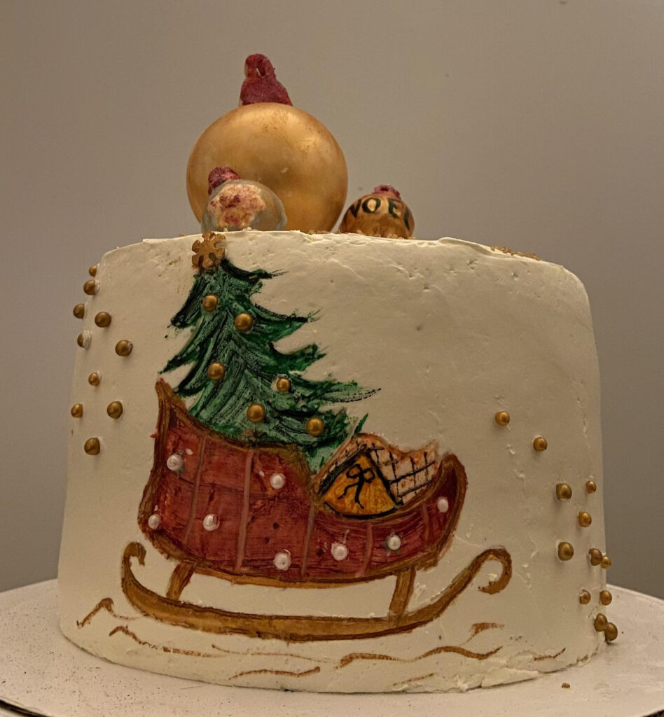A Kathy Kaneps white cake with a Christmas sleigh in frosting on the side and a few ornaments on top