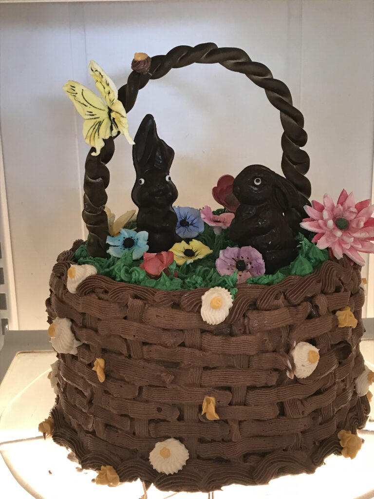 Kathy Kaneps cake in the likeness of an Easter basket with two chocolate bunnies inside, flowers of different colors, and a yellow butterfly