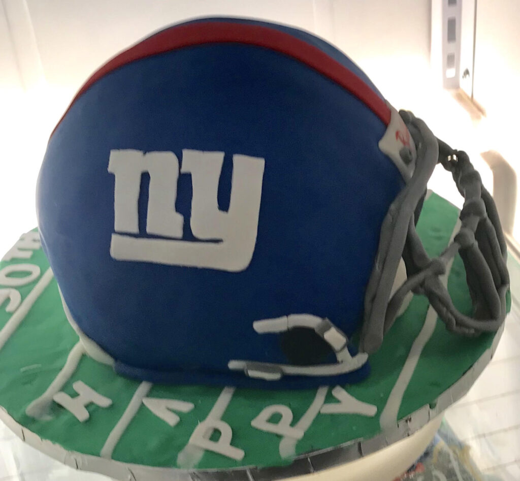 A Kathy Kaneps cake made to look like a New York Giants helmet on top of a football field