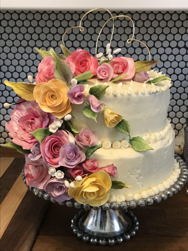 A Kathy Kaneps white cake with frosting flowers of different colors on it
