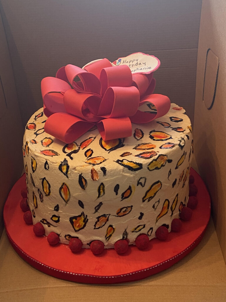 A Kathy Kaneps cake with a happy birthday pink ribbon made of icing on top