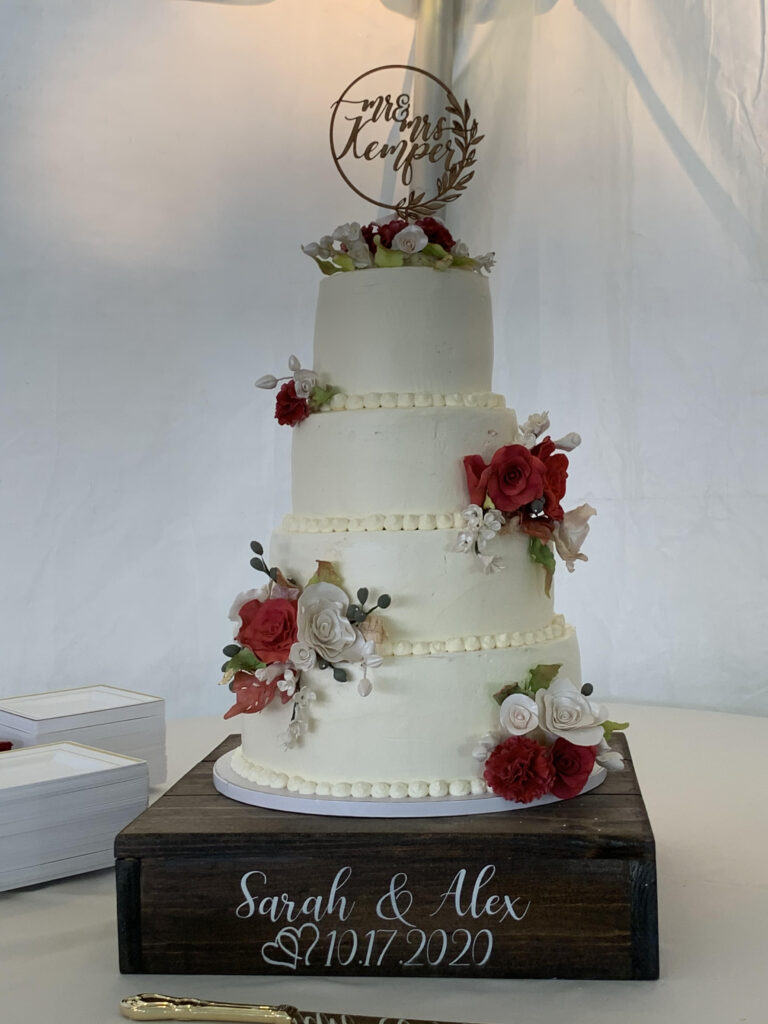 An elegant Kathy Kaneps white wedding cake with frosting flowers of red and white on the side