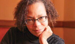 Author Lauret Savoy rests her head on her hand.
