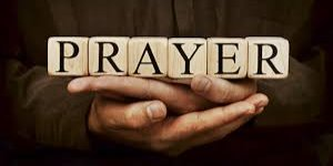 The word Prayer spelled out on Scrabble cubes held by hands