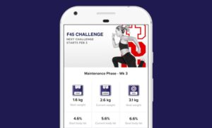 A smartphone with a woman runner on the screen and options within the F45 fitness app