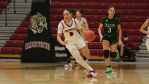 Jess Booth dribbles the ball upcourt during a women's basketball game.